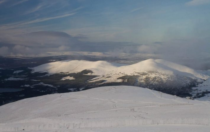 The view from Cairngorm mountain. Snow covered hills with a bit of blue sky and sunlight hitting the hilltops