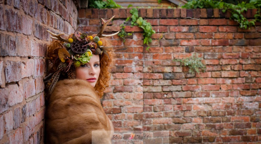 Female model with antler and floral head piece against a brick wall