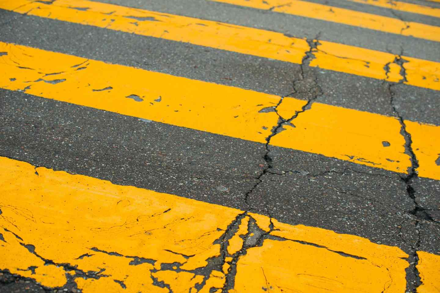 A road crossing in yellow across a grey cement road symbolising the colours of the year 2021 Ultimate gray and illuminating