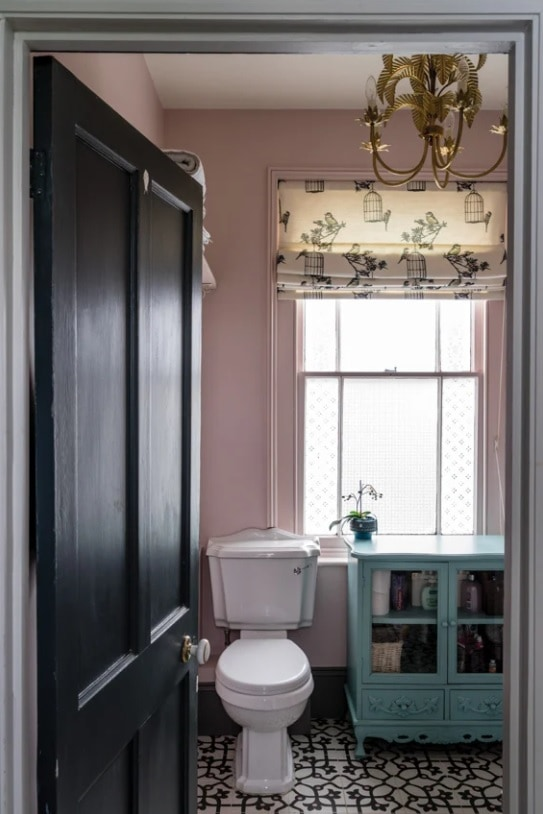 pink walls and black and white tiles in the bathroom
