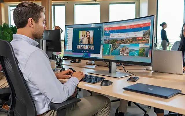 homem usando um monitor curvo para trabalhar