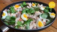 Een koekenpan met daarin een couscousgerecht van bloemkool met veldsla, makreel en gekookt ei.