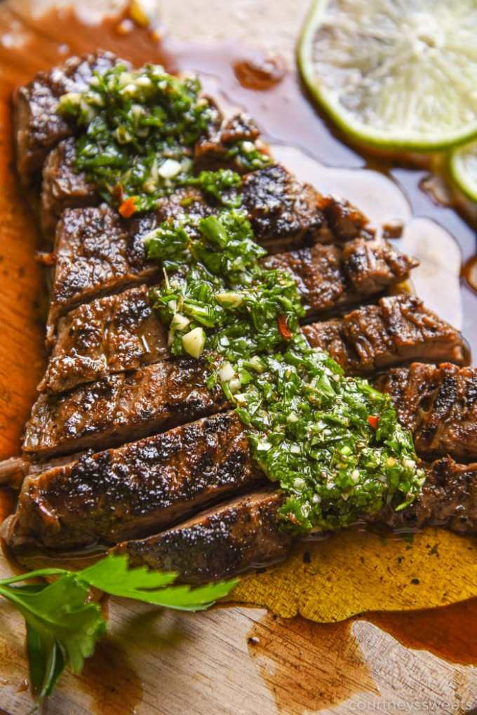 grilled steak with chimichurri sauce on a cutting board