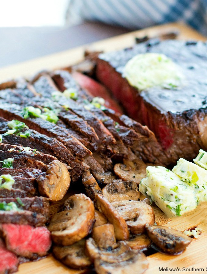 Teriyaki London Broil with Garlic Herb Butter on a cutting board