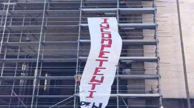 """Striscione con scritta """"Incompetenti""""contro le Istituzioni"""
