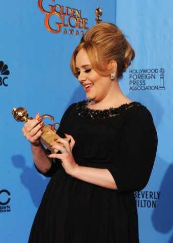 Adele guarda la statuetta appena vinta   © Kevin Winter/Getty Images