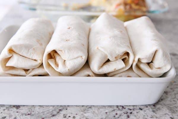white baking pan with rolled freezer breakfast burritos
