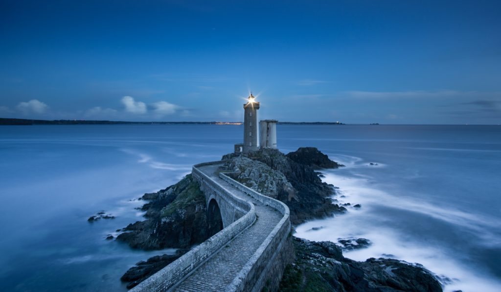 a lighthouse juts out into the water, perched on the edge of a cluster of jagged rocks