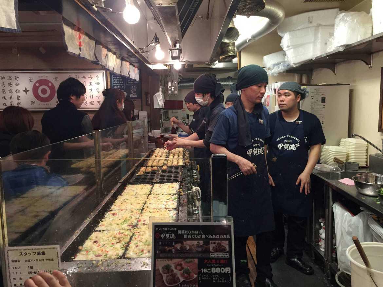 Cooks preparing takoyaki in Osaka, Japan