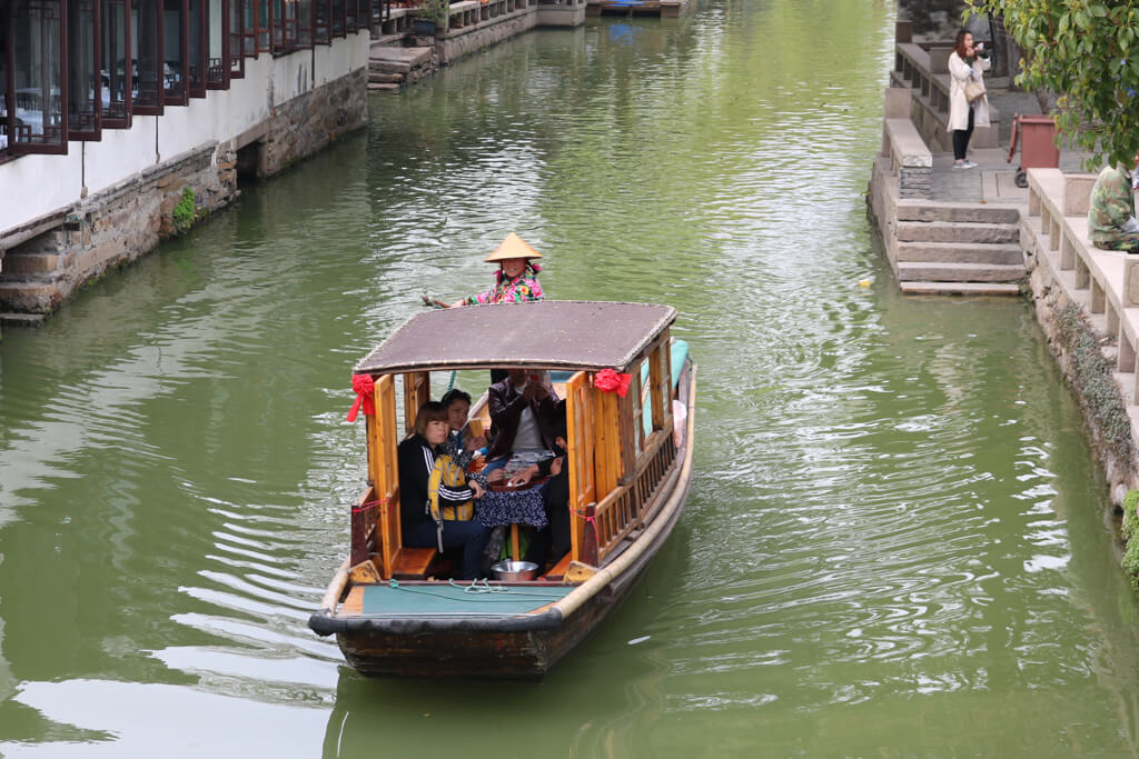 A boat rower rows a boat down a canal in Zhouzhuang, China