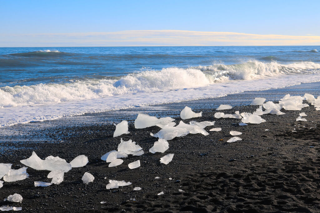Chunks of ice are washed onto a beach near Jökulsárlón glacial lagoon