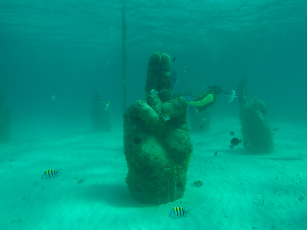 A sculpture of a hand at MUSA, near Cancun