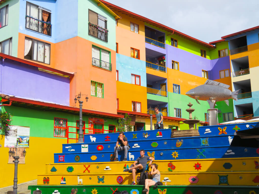 Bright buildings surround a public square in Guatape, Colombia