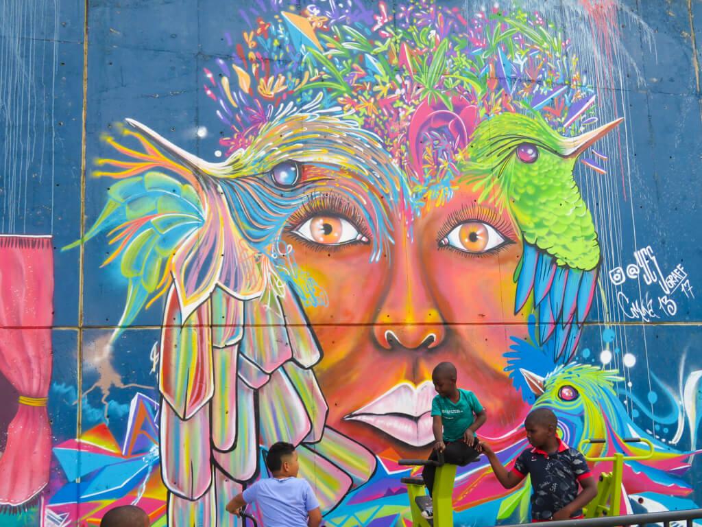 Children play next to a mural in Comuna 13, Medellin
