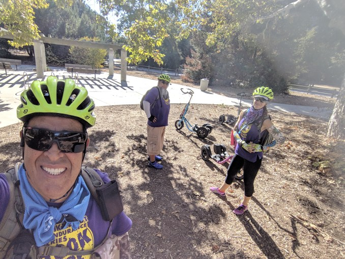Rider taking a selfie with two other riders and three Me-Movers in the background.
