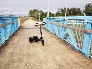 Black Me-Mover on a concrete trail over a bridge with light blue side rails