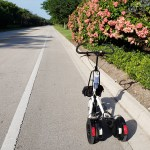 White Me-Mover on bike path alongside a Florida road with pink flowering bushes to the right.