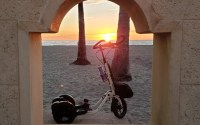 Looking through a window in a stone wall at a white Me-Mover on a beach at sunrise