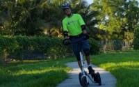 A man in a yellow shirt rides a silver Me-Mover on a winding Florida trail with palm trees and a fence in the background.