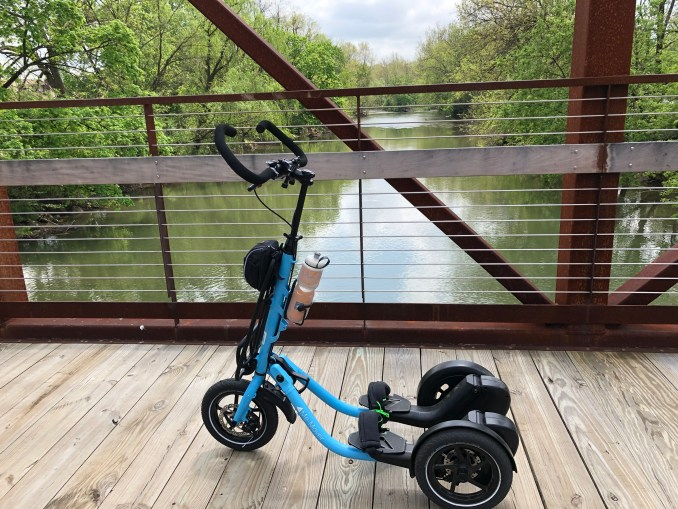 A blue Me-Mover on a trail bridge over the a creek with tree-lined banks.