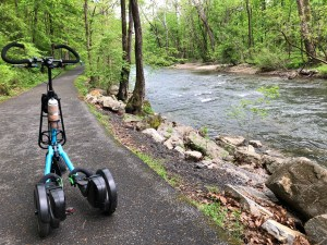 A blue Me-Mover on a trail alongside a creek with tree-lined banks.