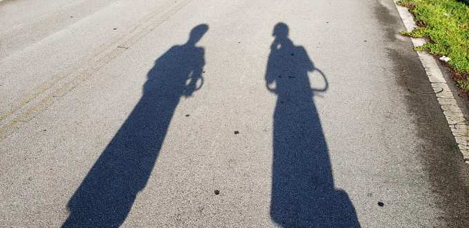Shadows of two Me-Mover riders on light colored pavement