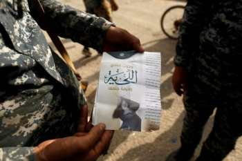 """An Iraqi soldier shows a pamphlet which reads """"Wearing beards is compulsory, shaving is prohibited"""" along a street of the town of al-Shura, which was recaptured from Islamic State (IS) on Saturday, south of Mosul, Iraq October 30, 2016. REUTERS/Zohra Bensemra/Files"""