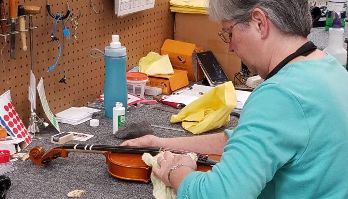 Repair technician cleaning a violin.