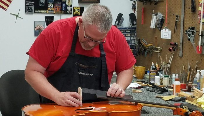 Repair technician replacing the bridge on a cello.