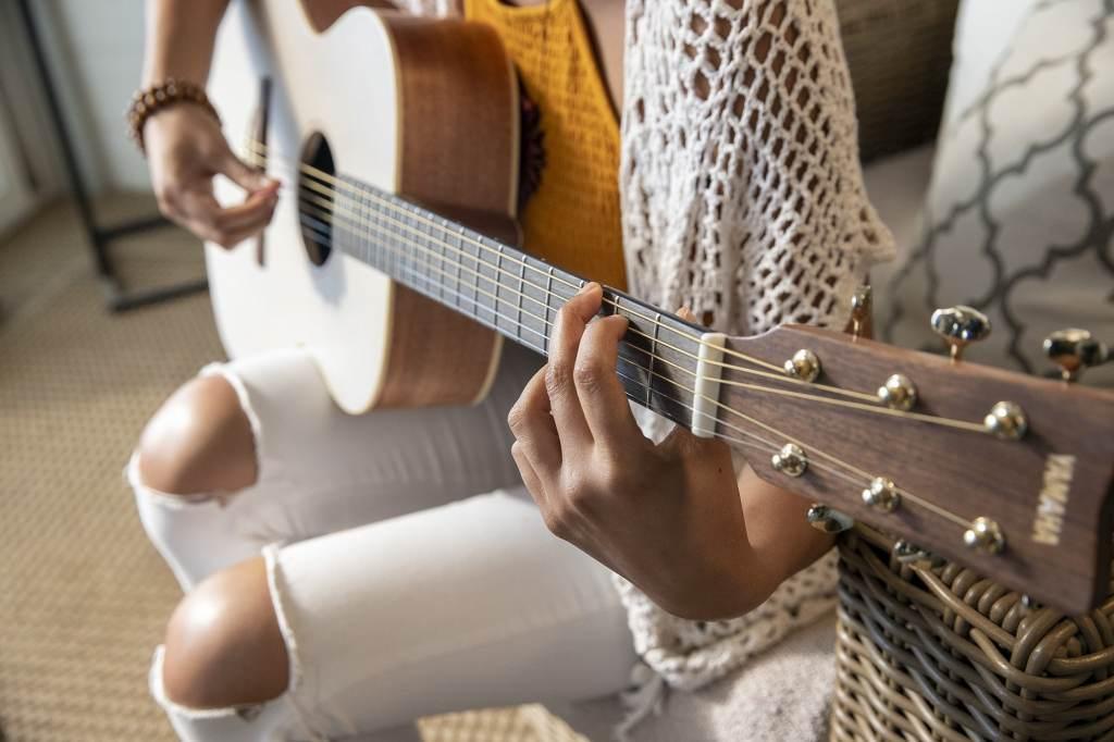 Close up of girls hands playing a yamaha storia guitar.