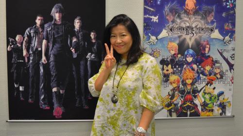 Yoko Shimomura posing in front of covers of her musical work.