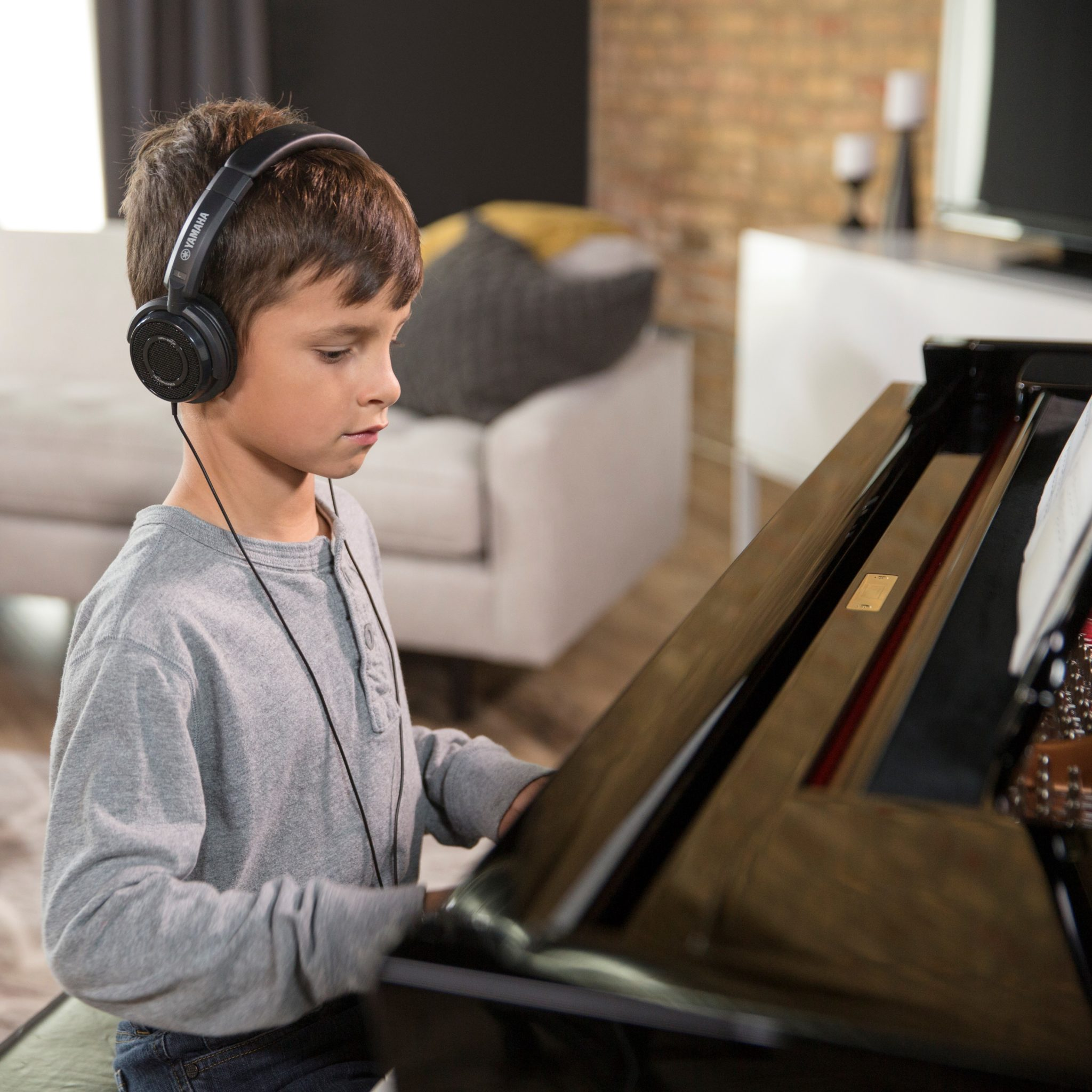 child with headphones playing piano