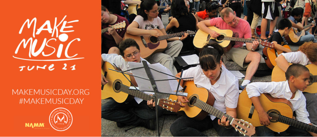 Group of people together, playing guitar on Make Music Day.