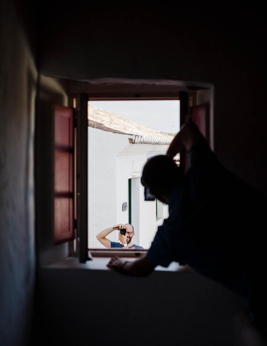 casamento aldeia de pedralva noivo e amigo fotografam-se à janela contraluz