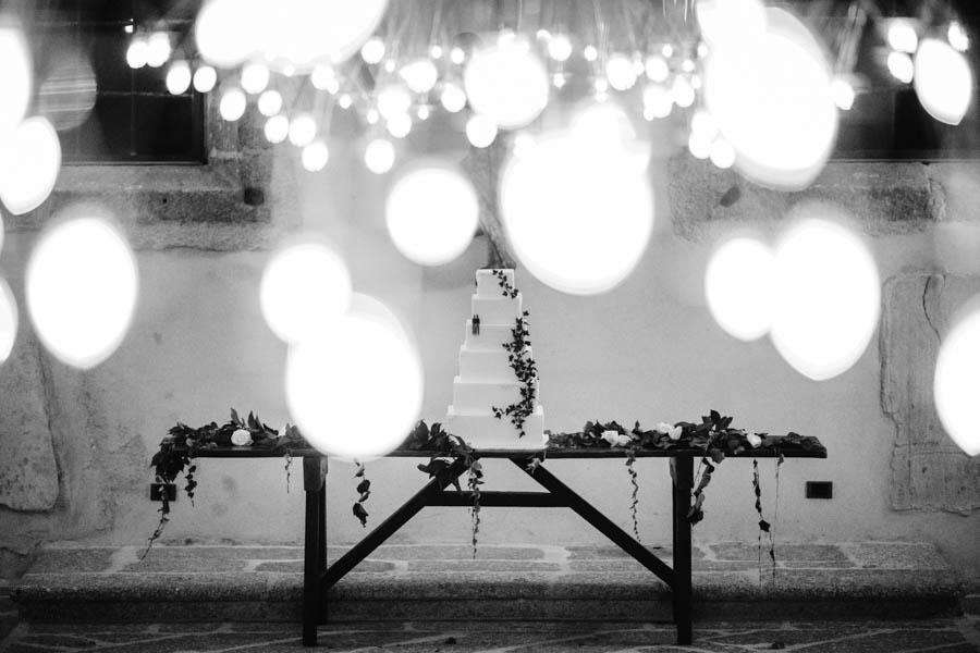 casamento gerês bolo de noivos sobre mesa decorada com hera e rosas brancas entre luzes