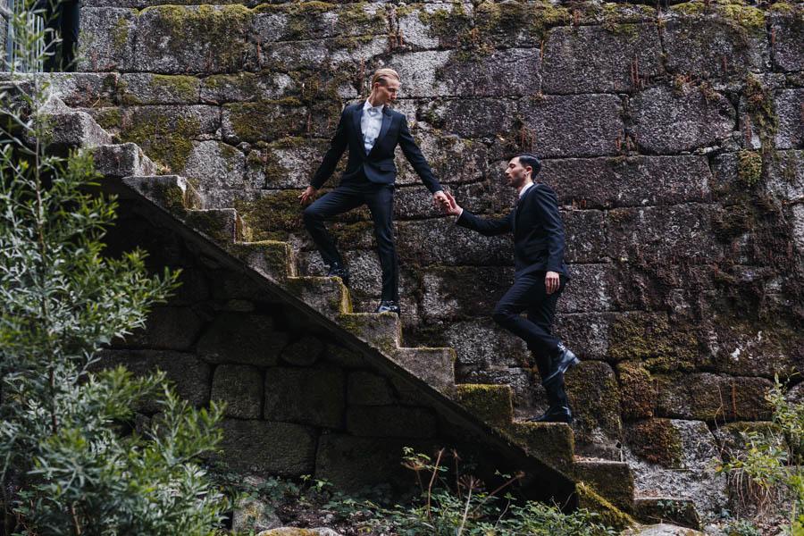 casamento gerês noivos com fato preto subindo escada de pedra de mãos dadas