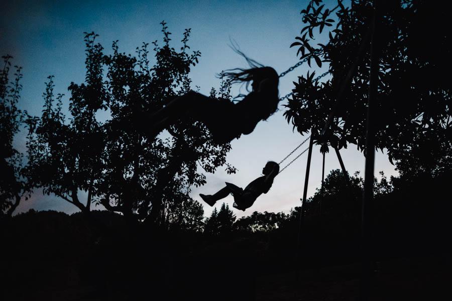 quinta de santana meninas andam de baloiço ao entardecer em contraluz