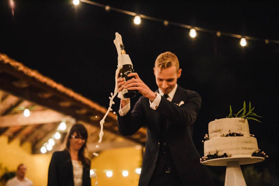 quinta de santana noivo abre garrafa de champanhe durante corte do bolo