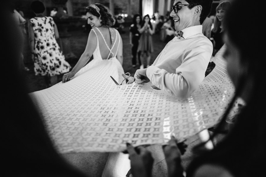 fotografia de casamento Landim noivo a cortar vestido da noiva