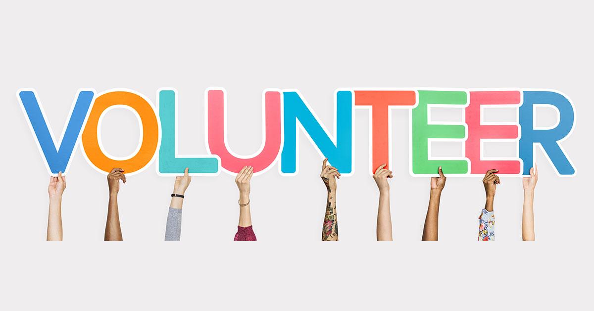 hands holding up a volunteer sign