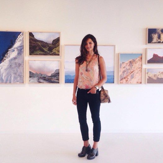 Meg Haywood-Sullivan poses in front of a gallery of her photography; Photo courtesy of Haywood-Sullivan