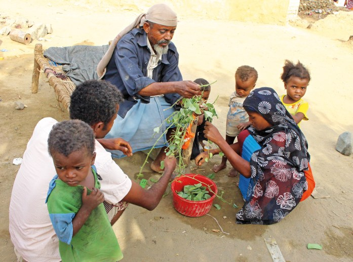 A man feeds children leaves. Three- quarters of Yemen's population now depends on aid, but many become desperate when food fails to reach their village.