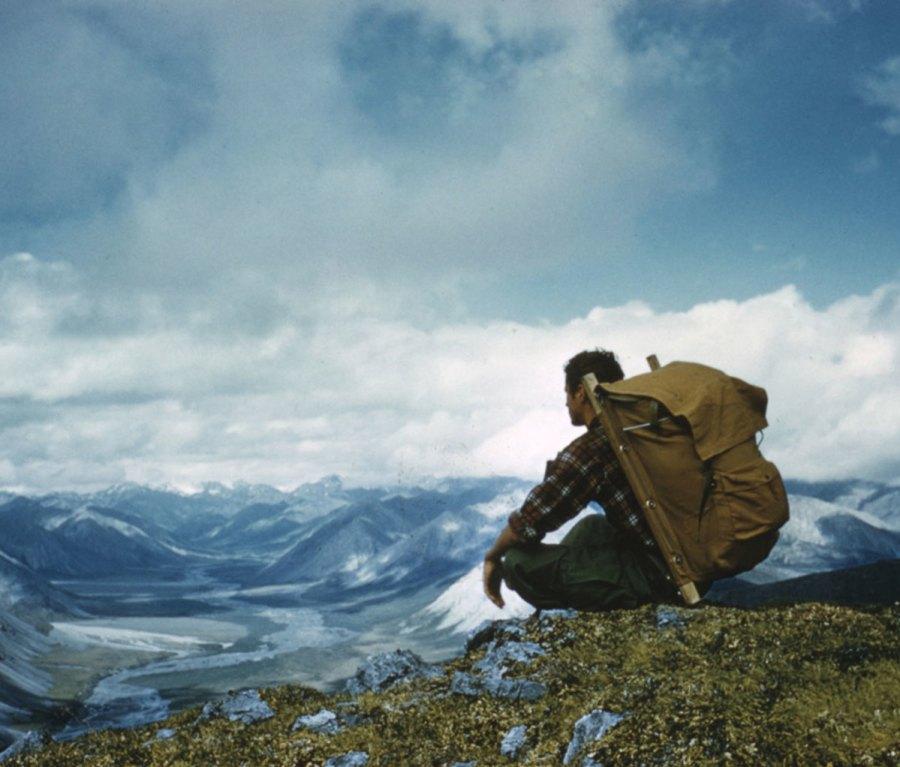 Backpacker sitting cross-legged on edge of cliff overlooking Alaskan mountain range