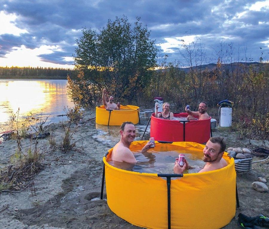 Men soaking in port-a-tubs along Yukon River.