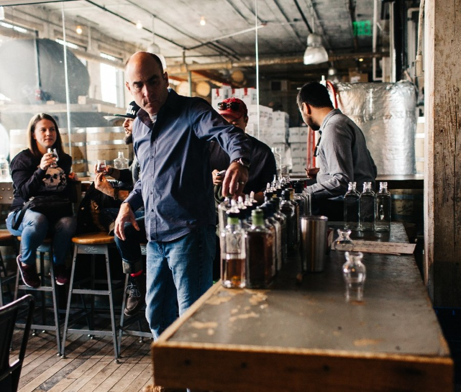 Patrons sample liquor and a man looks at a row of bottles at Journeyman Distillery in Three Oaks, Michigan.