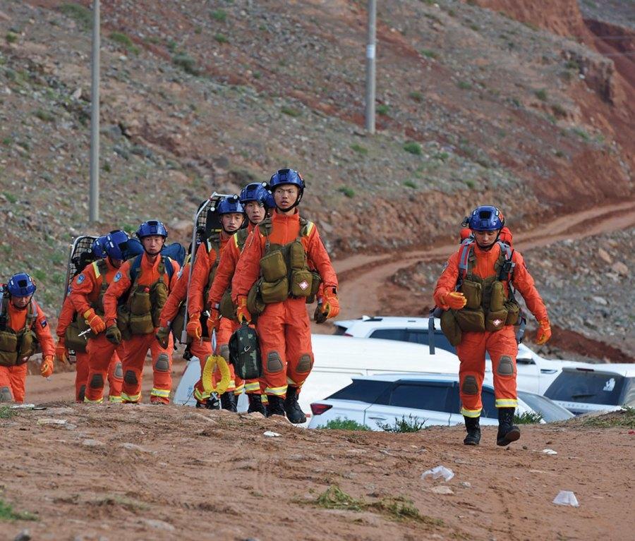 People in hazmat suits walking across dirt
