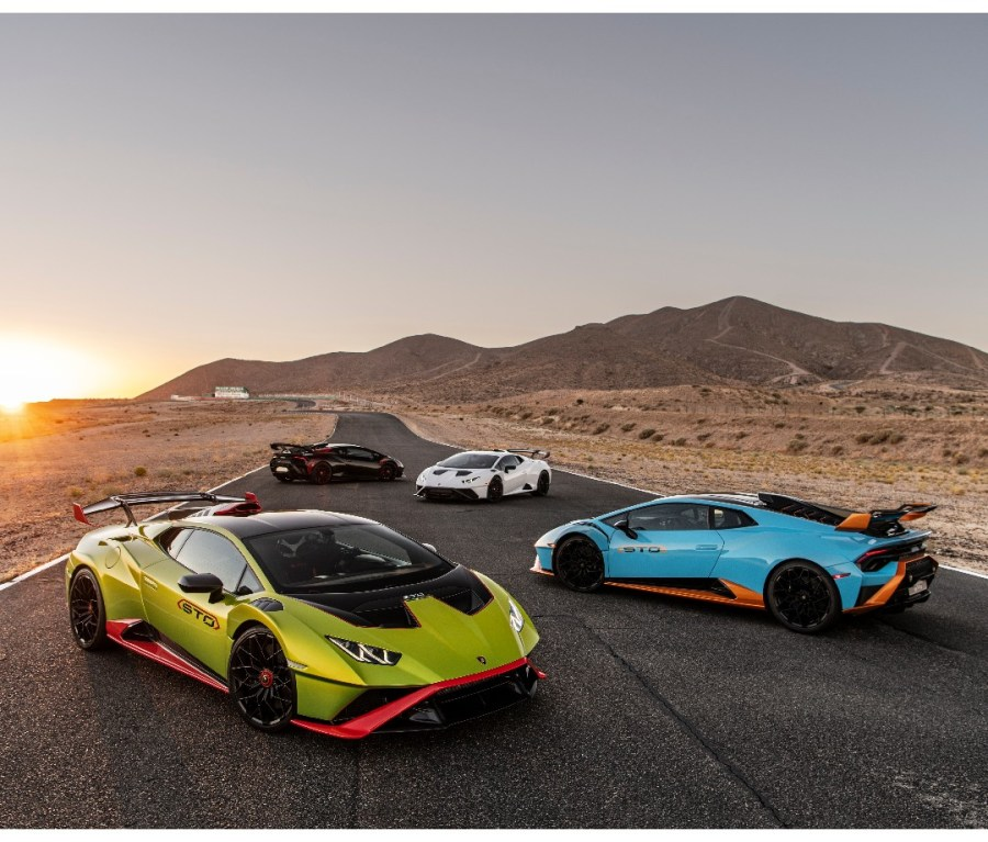 Four 2021 Lamborghini Huracán STOs parked on a race track at sunset. Colors: green, blue, white and black