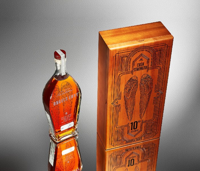 Bottle of whiskey next to box with wings etched on front