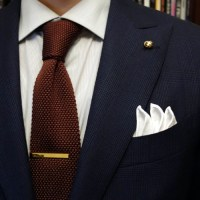 Gold colored classic tie bar with dark blue men suit ...