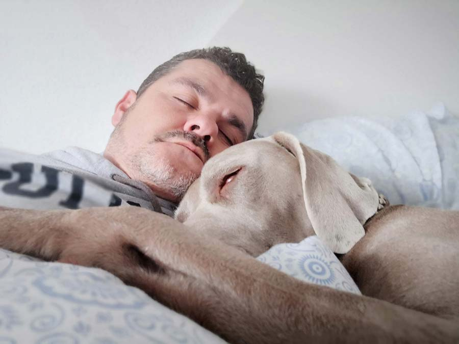 man sleeping with his dog